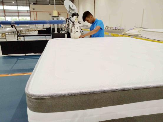 Malaysian worker operating automatic mattress tape edge machine